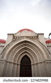 "Close up. The entrance to ""Chiesa Cattolica Parrocchiale S. Giuliano"" - Italian Catholic perish church of Saint Giuliano with red domes and gray stone walls. Cloudy sky. Messina, Sicily, Italy."