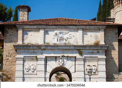 Close up. The entrance of Medieval castle (Castello di Brescia) with with a winged angry lion that holds a book. Brescia, Lombardy, Italy. Roman ancient castle. White marble.