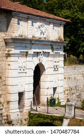 Close up. The entrance of Medieval castle (Castello di Brescia) with a bridge, sculptures and a statue of a winged lion that holds a book. Brescia, Lombardy, Italy. Roman ancient castle. White marble.