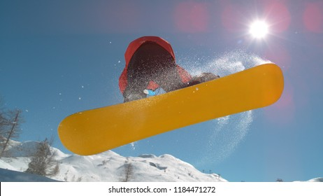 CLOSE UP: Extreme snowboarder jumping in big mountain ski resort. Detail of snowboard taking off the kicker in groomed snow park. Snowboarding jump on sunny winter day in snb park