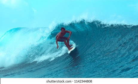 CLOSE UP: Extreme surfboarder rides an epic emerald colored barrel wave in sunny Teahupoo, Tahiti. Young pro surfer having fun riding the epic crystal clear tube waves in stunning French Polynesia.