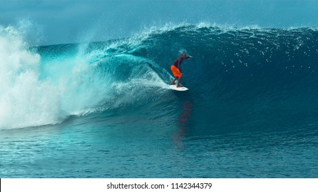 CLOSE UP: Fearless young pro surfboarder rides a glassy emerald ocean wave in breathtaking Tahiti. Spectacular shot of extreme sportsman surfing a big barrel wave crashing towards the sunny beaches.