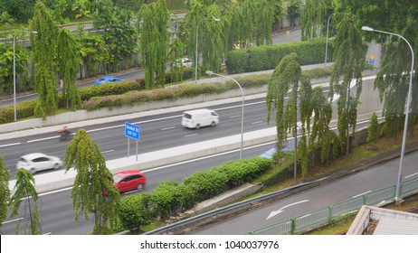 CLOSE UP: Flowing traffic on freeway in a busy city during daytime. People commuting to work from one part of the town to the other. Different vehicles speeding by on nearby highway. New age transport