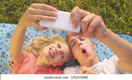 CLOSE UP: Funny close up shot of a young couple making goofy faces while video calling their friends. Young Caucasian couple lies on the blue blanket and takes selfies during their carefree date.