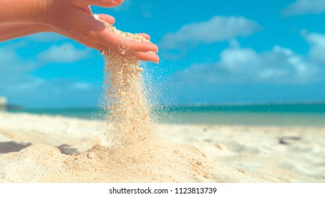 CLOSE UP: Gentle summer wind blows tiny grains of white sand out of playful woman's soft hand. Unrecognizable young female tourist plays with the hot sand on the exotic sunny beach in Cook Islands.