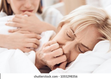 Close up. Girl is caring for elderly woman in bed at home. Woman is feeling bad, girl is concerned.