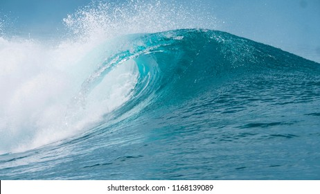 CLOSE UP: Glassy droplets of ocean water fly away from spectacular tube wave crashing near a tropical beach in Teahupoo, Tahiti. Perfect emerald barrel wave breaks and splashes into the blue sky.