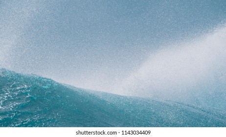 CLOSE UP: Glassy water sparkles in the sun as tiny droplets fly away from large barrel wave coming from vast Pacific Ocean. Beautiful deep blue ocean wave splashing near sunny coast of exotic island