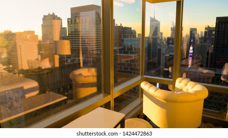 CLOSE UP: Golden morning sunshine illuminates the hotel room with a breathtaking view of the metropolitan city. Breathtaking view of downtown New York at sunrise from a hotel room above the city.