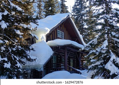 CLOSE UP: Golden winter sunbeams shine on a rustic cottage in the middle of a snowy forest under a rocky mountain in Alberta, Canada. Picturesque shot of a lodge hidden in forest under a mountain.