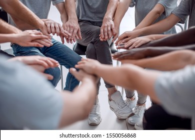 close up. a group of diverse young people holding hands