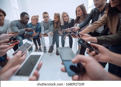 close up. groups of young people with smartphones sitting in a circle