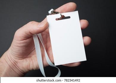 Close up, hand holding Identification white blank plastic id card, mockup.