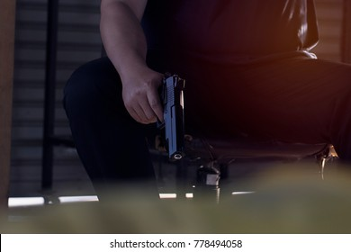 Close up, Hand of a man carrying a magazines gun. There is a bullet in the chamber. Prepare to used protect yourself. He dodged in a dark room with sunlight. Blur and soft focus.