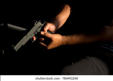 Close up, Hand of a man carrying a magazines gun. There is a bullet in the chamber. Prepare to used protect yourself. He dodged in a dark room with sunlight. Soft focus.