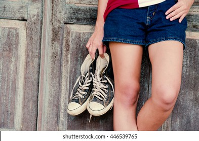 Close up, Hand woman holding shoes a standing with wooden background