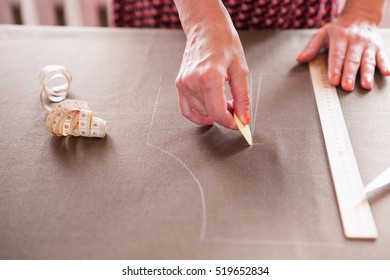 Close up. hands woman Tailor working cutting a roll of fabric on which she has marked out the pattern of the garment she is making with tailors chalk.
