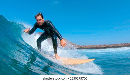 CLOSE UP: Happy Caucasian male surfer riding a wave and giving the camera the shaka sign. Young surfboarder riding a wave on a perfect summer afternoon in Canary Islands. Fun summer vacation sport.