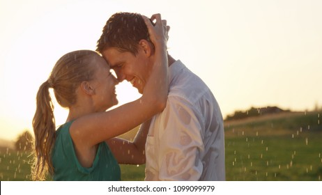CLOSE UP: Happy young woman runs her fingers through boyfriend's wet brown hair while dancing in the middle of tranquil meadow on a rainy summer evening. Beautiful couple dancing at romantic sunrise.