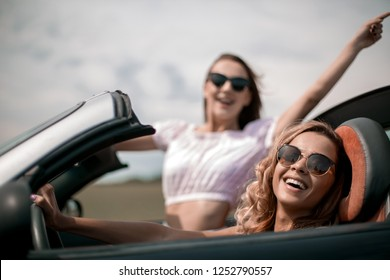close up.two happy young women in a convertible car