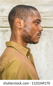 Close up, head short of Young African American Man with beard in New York, wearing green shirt,  collar unbuttoned, standing against white marble wall, seriously looking forward. Right Side View