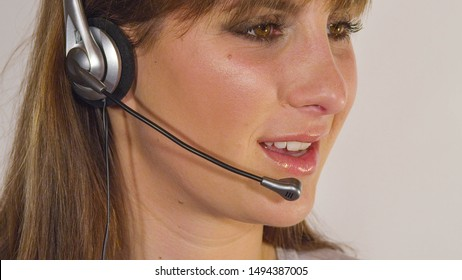 CLOSE UP: Helpful call centre agent talking to potencial clients. Female tech support worker using a headset for answering customer calls. Emergency operator taking calls from people in distress.