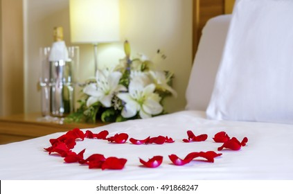 Close up, honeymoon bed with focus on the heart-shaped rose petals. White bedding, flowers, champagne flutes, honeymoon set up