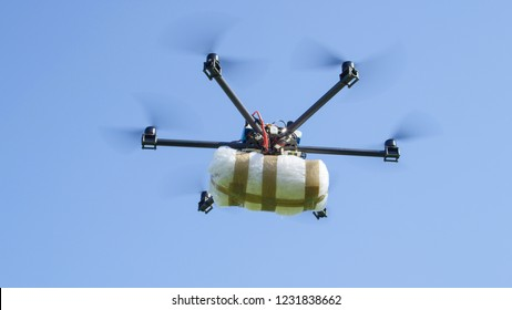 CLOSE UP: Illegal cargo drone flying big narco drugs package against blue sky