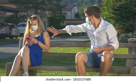 CLOSE UP: Irritated man frantically moves away after stranger sits next to him on a public bench while he texts from the park. Two millennials social distance while fiddling with smartphones at park.