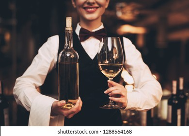 Close up. Joyful elegant waitress holding bottle of red wine and glasses, standing near bar. Sommelier tasting wine in restaurant.