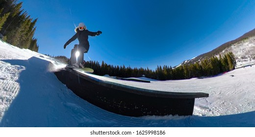 CLOSE UP, LENS FLARE: Active woman on a snowboarding vacation slides along a railing placed in a ski resort snow park. Cool action shot of woman doing a railslide while snowboarding on Copper Mountain