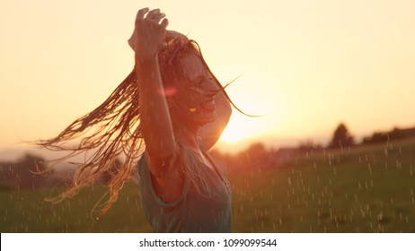 CLOSE UP, LENS FLARE: Attractive blonde haired woman playfully spins in the soothing summer rain. Young Caucasian female dancer dances in the rain on a picturesque spring evening in the countryside.