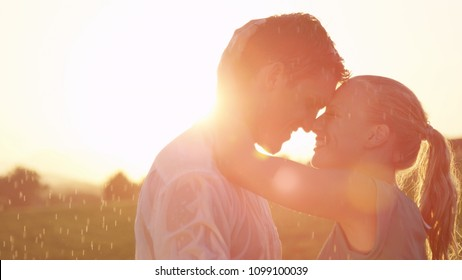 CLOSE UP, LENS FLARE: Beautiful blonde girl wraps her arms behind her handsome boyfriend's head as they dance in the cool rain at sunset. Lovely Caucasian couple dancing in the unexpected summer rain.