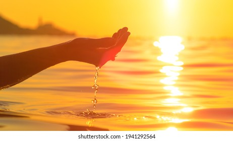 CLOSE UP, LENS FLARE, DOF: Unrecognizable female tourist on summer vacation lifts up a handful of crystal clear ocean water at sunrise. Sunset shines on woman's hand cupping a handful of sea water.