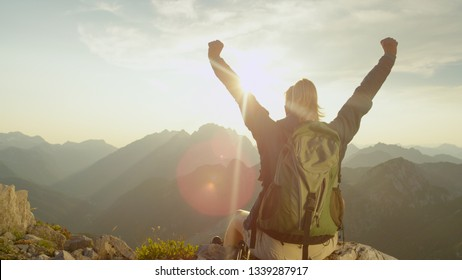 CLOSE UP, LENS FLARE: Ecstatic trekker girl celebrates reaching the mountaintop with a breathtaking view of the mountain range on a sunny summer day. Unrecognizable hiker woman outstretches arms.