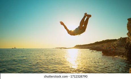 CLOSE UP, LENS FLARE: Fit male tourist dives into the refreshing ocean water at sunset. Athletic man on a relaxing summer vacation in Mediterranean dives off a rocky cliff on a perfect summer evening.