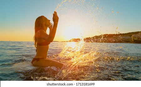 CLOSE UP, LENS FLARE: Gorgeous smiling surfer girl lifts her arms in the air and splashes glassy water while sitting on her surfboard and observing the sunlit landscape. Happy woman on summer vacation