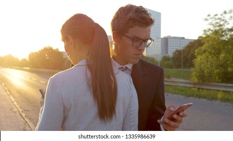CLOSE UP, LENS FLARE: Handsome Caucasian man walking to work and texting crashes into the annoyed businesswoman. Clumsy man and woman looking at their phones bump into each other in the sunny city.