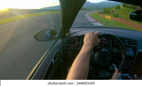 CLOSE UP, LENS FLARE: Man enjoying a sunny day by driving his sportscar along closed track. Race car driver speeding along empty track on a sunny day. Unrecognizable racer warming up for time trial