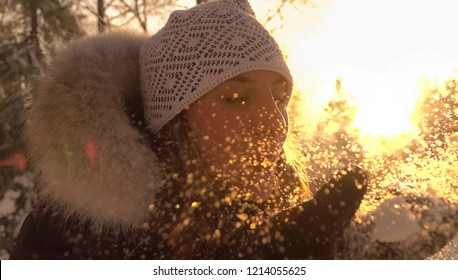 CLOSE UP, LENS FLARE: Playful Caucasian girl blows a handful of snow in the sunny air. Cheerful female tourist playing in the Scandinavian forest on a sunny winter morning. Carefree woman in winter.