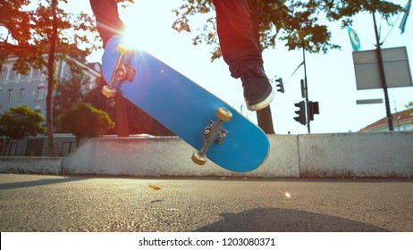 CLOSE UP, LENS FLARE: Unrecognizable male athlete does a fakie trick with his blue skateboard on sunny day at the park. Young skater rolling down the pavement jumps and does a flip with his deck.