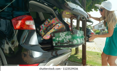 CLOSE UP, LENS FLARE: Young female tourist's luggage falls out of the back of her black SUV parked in front of her home in the sunny suburbs. Heavy travel bags fall out of cheerful woman's big car.