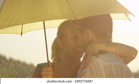 CLOSE UP: Love struck woman and man looking into each other's eyes while hiding from the spring rain under small yellow umbrella. Cute young couple dances outdoors during a refreshing summer shower.