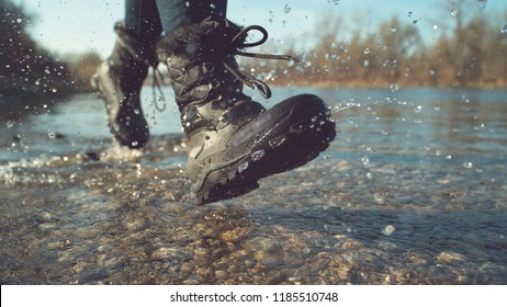 CLOSE UP, LOW ANGLE, DOF: Energetic young woman in fuzzy black boots playing by the tranquil stream on a lovely autumn day. Unrecognizable playful hiker girl running and splashing pure river water.