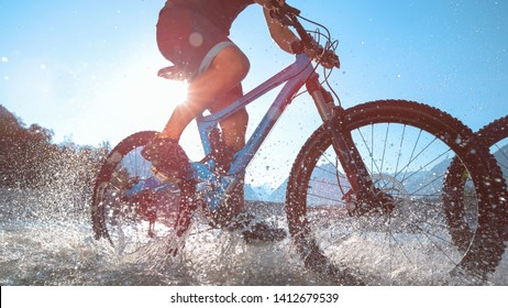 CLOSE UP, LOW ANGLE, LENS FLARE: Glassy drops of water splash at camera as the unrecognizable man cycles along the beautiful Soca river on a sunny summer day. Male tourists riding ebikes in a stream.