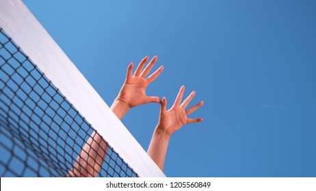 CLOSE UP, LOW ANGLE: Unrecognizable athletic woman's hands stretch over the volleyball net on a sunny day. Unknown fit female playing volleyball sets up a block at the net to defend a spiked ball.