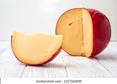 Close up, macro. Sliced piece of cheese Edam and dutch head of cheese on white wooden background.