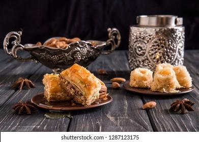 Close up, macro. Still life. Eastern honey sweets. Turkish  traditional baklava with pistachios and baklava bird's nest. Dark wooden background.