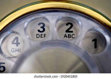 Close up, macro view of retro, vintage rotary dial telephone. Gold metal trim with clear dialing plate. For concepts related to technology, communications, innovation, old, antique, and obsolete.