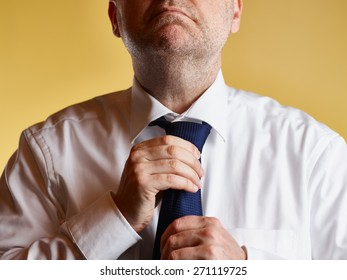 Close up, male wearing white shirt and blue tie, he tighten the tie knot, yellow background